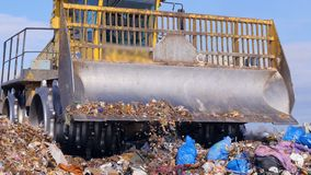 A close view on a landfill truck near a full garbage truck. A close-up of a landfill compactors blade with a full garbage truck in the background stock video