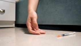 Close-up langzame geanimeerde video van hand met syring die op vloer vallen Concept dood door drugs of narcoticaoverdosis stock video