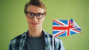 Close-up langzame motie van het glimlachen van kerel Britse vlag houden die golvend in wind stock footage