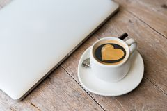 Close up of laptop and coffee cup with heart shape Royalty Free Stock Photo