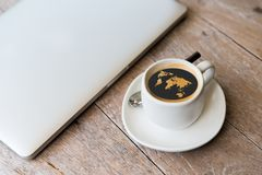Close up of laptop and coffee cup with world map Stock Photo