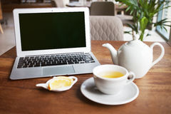 Close-up of a laptop computer with blank screen. And cup of green tea with lemon on a wooden table to start working morning in urban life. Browsing Internet Stock Photos