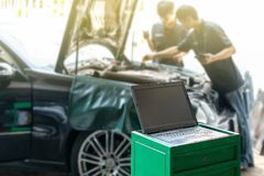 Close up laptop or computer notebook interfaced with car for repair during two repairman work investigate problem program and. Electric check automobile stock images