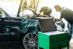 Close up laptop or computer notebook interfaced with car for repair during two repairman work investigate problem program and. Electric check automobile stock photography