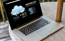Close up of laptop computer on table at hotel. Technology, weather cast, business and modern life concept- close up of open laptop computer with meteo forecast Royalty Free Stock Photos