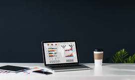 Close-up of laptop with graphs, charts and diagrams on screen on white table. Nearby is tablet computer, smartphone, paper graphics, cup of coffee. In royalty free stock photography