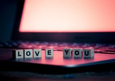 Close up of laptop and love message in stay connected, online dating or shopping for Valentines day. Conceptual image of text Love you in wood blocks on computer royalty free stock image