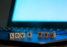 Close up of laptop and love message in stay connected, online dating or shopping for Valentines day. Conceptual image of text Love you in wood blocks on computer royalty free stock photos