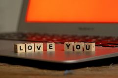 Close up of laptop and love message in stay connected, online dating or shopping for Valentines day. Conceptual image of text Love you in wood blocks on computer stock images