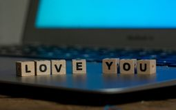Close up of laptop and love message in stay connected, online dating or shopping for Valentines day. Conceptual image of text Love you in wood blocks on computer stock photos