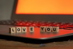 Close up of laptop and love message in stay connected, online dating or shopping for Valentines day. Conceptual image of text Love you in wood blocks on computer royalty free stock images