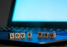 Close up of laptop and love message in stay connected, online dating or shopping for Valentines day. Conceptual image of text Love you in wood blocks on computer royalty free stock photography