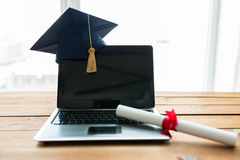 Close up of laptop with mortarboard and diploma. Education, graduation, technology and e-learning concept - close up of laptop computer with mortarboard and Stock Images