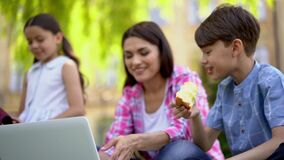Mother use laptop to teach children outdoors