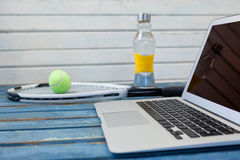 Close up of laptop by tennis racket and balls with water bottle against white wall Royalty Free Stock Photos