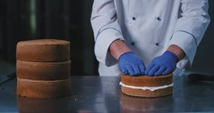 A close up of a large baker in chefs attire topping the bottom half of the creamed cake with the top non creamed half. Then moving it aside, the cake looking stock video