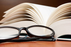 Close up of large book pages and glasses. Stock Photography