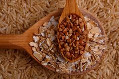 Collecting dry cereals. Buckwheat, rice, oatmeal in a large brown plate. Close-up in a large brown plate with rice is a large spoon with oat flakes, on the royalty free stock images