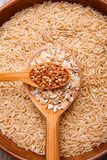 Collecting dry cereals. Buckwheat, rice, oatmeal in a large brown plate. Close-up in a large brown plate with rice is a large spoon with oat flakes, on the stock photos
