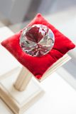 Close up of large diamond on red pillow. At jeweler's shop. Concept of wealth and luxurious life Stock Images