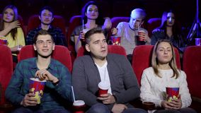 Close-up of a large group of people watching a scary movie in the cinema. stock video