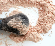 Close-up of large makeup brush with loose cosmetic powder on white background. Side view. Stock Images