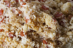 Couscous. Close up of a large plate of cousous mixed with tomato and peppers Stock Images