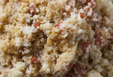 Couscous. Close up of a large plate of cousous mixed with tomato and peppers Royalty Free Stock Photos