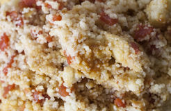 Couscous. Close up of a large plate of cousous mixed with tomato and peppers Royalty Free Stock Photography