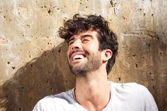 Close up laughing carefree man sitting by concrete wall. Close up portrait of laughing carefree man sitting by concrete wall Stock Image