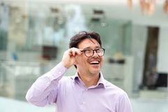 Close up laughing man in glasses looking away stock photo