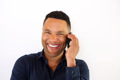 Close up laughing young african man talking on cell phone. Close up portrait of laughing young african man talking on cellphone against white background royalty free stock images