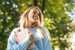Close up of laughing young girl student. With backpack carrying books, walking at the park Royalty Free Stock Images