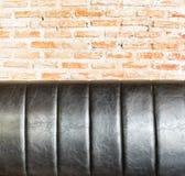 Close up Leather sofa at orange brick wall Royalty Free Stock Image