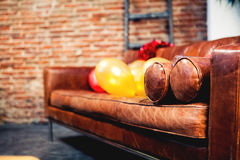 Close up of leather sofa with party balloons. Brick wall background. Royalty Free Stock Photos
