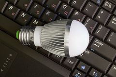 Close up Led Bulb at the keyboard background. Royalty Free Stock Images
