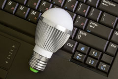Close up Led Bulb at the keyboard background. The new generation of lamps. Economical and environmentally friendly Royalty Free Stock Photography