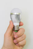 Close up Led Bulb at the man hand. Vertical. The new generation of lamps. Economical and environmentally friendly Stock Photography