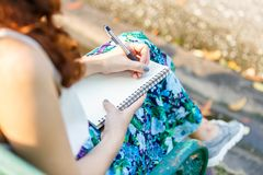 Close up left hand asian women with pen writing notebook and sitting on a wooden bench and a park royalty free stock images