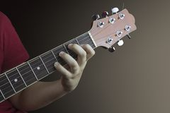 Close-up of the left hand of a young guitarist on the neck of an acoustic guitar. Photo taken on a brown background royalty free stock images