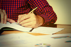 Close up left hand of young man writing and thinking about cost. At home Royalty Free Stock Photo