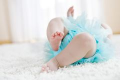 Close up of legs and feet of baby girl on white background wearing turquoise tutu skirt. Cute little child laughing and smiling. Happy carefree baby. Childhood Stock Images