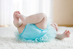 Close-up of legs and feet of baby girl on white background wearing turquoise tutu skirt. Cute little child laughing and smiling. Happy carefree baby. Childhood Stock Photos