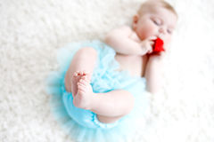 Close-up of legs and feet of baby girl on white background wearing turquoise tutu skirt. Cute little child laughing and smiling. Happy carefree baby. Childhood Royalty Free Stock Photos