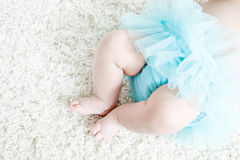 Close-up of legs and feet of baby girl on white background wearing turquoise tutu skirt. Cute little child laughing and smiling. Happy carefree baby. Childhood Stock Image