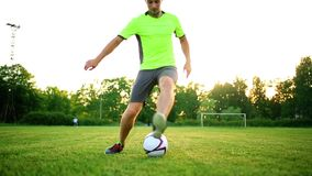 Close up legs and feet of football player in action wearing black shoes running and dribbling with the ball playing on