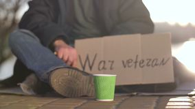 Close-up legs and hands of begging war veteran. Close-up of legs, hands and cardboard sign of disabled war veteran asking for help on the pavement. Homeless man stock video footage