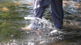Close up legs and hands of young woman scoops up and play the water. In the creek lonely stock video footage