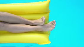 Close up of legs on inflatable mattress playing with water in pool, vacation. Stock footage stock footage