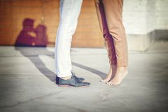 Close-up of legs of the kissing couple with shadows royalty free stock photography